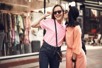 Positive beaming girl kissing cheerful friend in cheek. They walking together at street