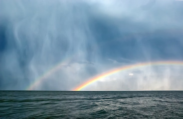 two rainbow in the rain over the water. mountain views and sunlight in drops of rain © Lyubov Furs