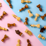 Scattered chess pieces. Pink and blue background. Flat lay concept. Pastel shades