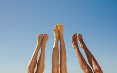 Close up of legs of three women raised up in the air