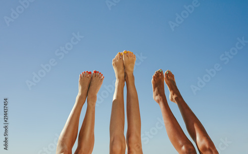 Close up of legs of three women raised up in the air - 214437454