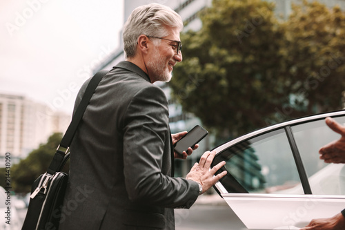 Fototapeta Happy mature commuter getting into a taxi
