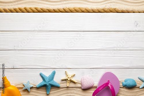 Beach accessories, hawser and seashells on white wooden board