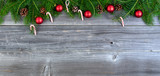 Christmas fir tree branches with seasonal decorations on weathered wood for holiday concept