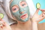 Skin care. Cheerful attractive caucasian female with clay mask on face and cucumber slices in hands against blue background getting beauty treatment. Spa concept with copy space