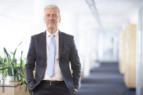 Fridge magnet Executive senior manager portrait. A senior businessman standing at the office while looking at camera and smiling.