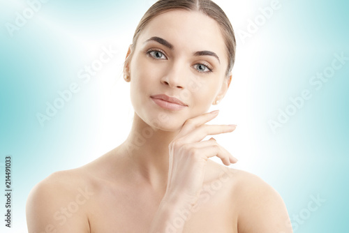 Foto Murales Portrait of a beautiful young woman with naked shoulders smiling while posing at isolated light blue background. Face beauty skin care. Natural make up