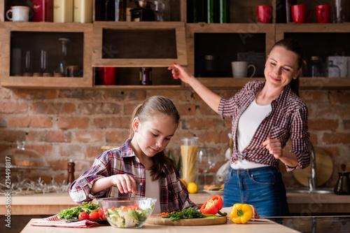 Foto Murales healthy family eating lifestyle. mom and daughter preparing vegetable salad.