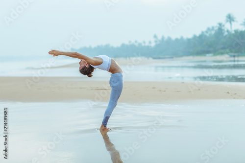 Leinwandbild Motiv Caucasian woman practicing yoga at seashore of tropic ocean