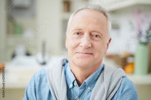 Leinwandbild Motiv Mature grey-haired man in denim shirt looking at you while sitting in the kitchen