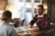 Young employee looking at colleague in front of him during discussion of working plans and moments