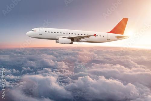 Leinwandbild Motiv Commercial airplane flying above dramatic clouds.