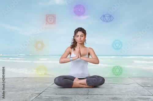 Obraz na płótnie Young woman is meditating on the beach with chakras glowing around her