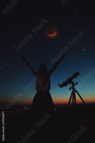 Girl looking at lunar eclipse through a telescope.