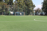 Marking a green artificial football field with a grass cover in the city stadium. The place for conducting competitions and sporting events. Landscape design of a sports complex
