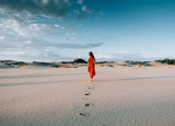 girl in a red dress goes into the distance in the desert