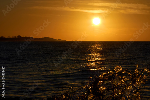 Foto Spatwand Chocoladebruin Seascape during sunset, dark water with golden sun path and even