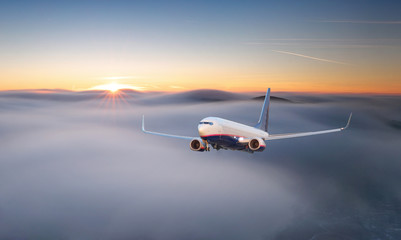 Passenger airplane. Landscape with big white airplane is flying in the red sky over the clouds and sea at colorful sunset. Passenger aircraft is landing at dusk. Business trip. Commercial plane. © TTstudio