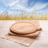 Pizza board with tableclothe on wooden desk. Field and blue sky as background. Top view mock up. Selective focus. - 214560452