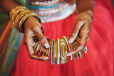 The hand with mehndi of Indian bride holding a lot of glitter bracelets (bangle) with red legenha background, close-up