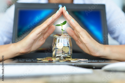 Growth of online money from e-business, with woman's hands protecting cash coins on laptop