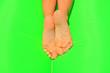 Leinwandbild Motiv Female feet with sand and green background