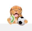 Leinwandbild Motiv Funny dog holding money and soccer ball in his paws above white banner. isolated on white background
