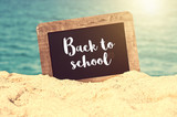 Back to school written on a vintage chalkboard in the sand of a beach - 214584831