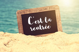 C'est la rentrée (meaning Back to school in French) written on a vintage chalkboard in the sand of a beach - 214584883