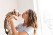 Leinwandbild Motiv Cheerful young woman playing with dog
