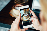 Close-up of female hands holding mobile phone. Woman making photo of cup of coffee at the table at cafe