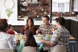 Multi Generation Family Praying Before Meal Around Table At Home - 214592422