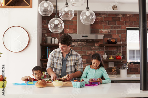 Children Helping Father To Make School Lunches In Kitchen At Home - 214593086