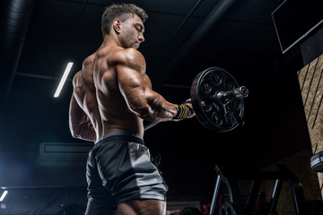 A young brutal male athlete is a bodybuilder with a perfect abs, exercising in the gym. Concept - strength, bodybuilding, styrodes, weightlifting, diet, muscles, sports nutrition, personal trainer