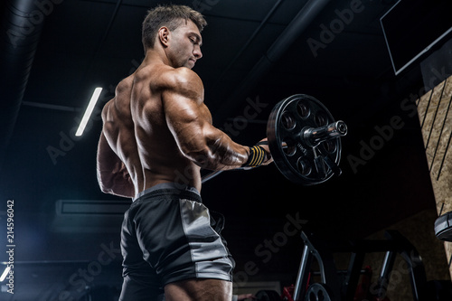 A young brutal male athlete is a bodybuilder with a perfect abs, exercising in the gym. Concept - strength, bodybuilding, styrodes, weightlifting, diet, muscles, sports nutrition, personal trainer © romanolebedev