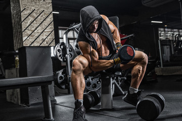 The brutal man is training the biceps on the bench, using a dumbbell. Concept - personal trainer, diet, sports nutrition, crossfit, styrodes, dumbbells, bodybuilding, weightlifting, gym. © romanolebedev