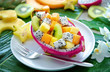 Leinwanddruck Bild - Exotic fruit salad served in half a dragon fruit on palm leaves