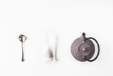 Tea in a disposable filter bag for brewing next to a gray cast iron kettle and a spoon on a white background. Top view. Flat lay - 214599213