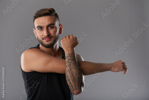 Handsome young sportsman with tattoo smiling at camera while stretching muscles of hands on gray background