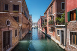 Traditional canal street and colorful Venetian houses in Venice, Italy.