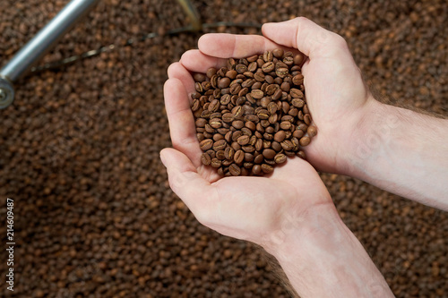 Leinwandbild Motiv Top view of hands holding handful of freshly roasted coffee beans over coffee background