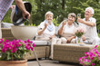 Smiling elderly people drinking wine during grill party in the garden