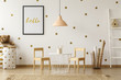 Bright and natural interior of a kindergarten room with a small table and wooden chairs against the wall with dot stickers and poster. Real photo