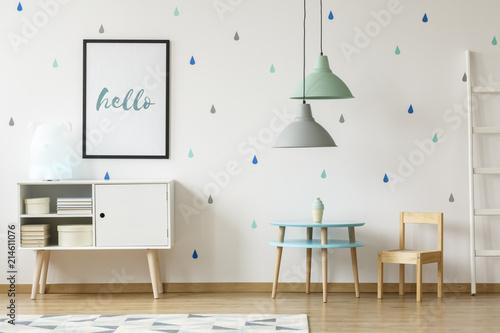 Prawdziwe zdjęcie pastelowego niebieskiego i miętowego pokoju dziecięcego z plakatem nad białą szafką stojącą obok okrągłego drewnianego stołu