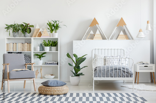 Real photo of patterned armchair with open book and wicker footrest with pillow placed in bright bedroom interior with green plants, metal bed and wooden mountain shape decor
