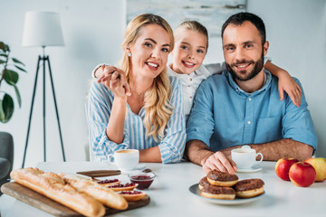 happy young family with breakfast on table looking at camera