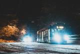 winter city night scene tram stop in snowstorm