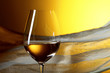 Glass of white wine on a yellow background.