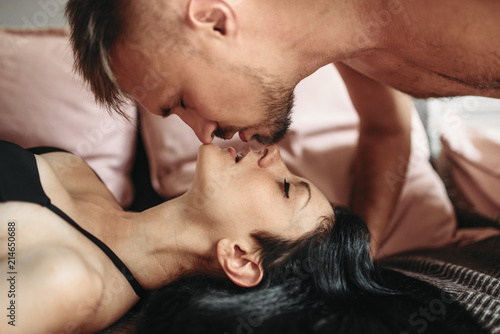 Leinwanddruck Bild Sexy couple kissing on couch, erotica in bed