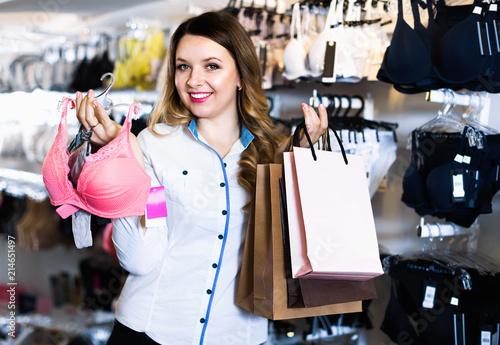 Leinwandbild Motiv Female shopper boasting her purchases in underwear shop